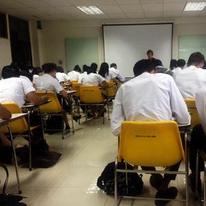 Studenten auf gelben Plastikstühlchen mit angebauten Minitüschchen, die eher nicht Laptoptauglich sind...