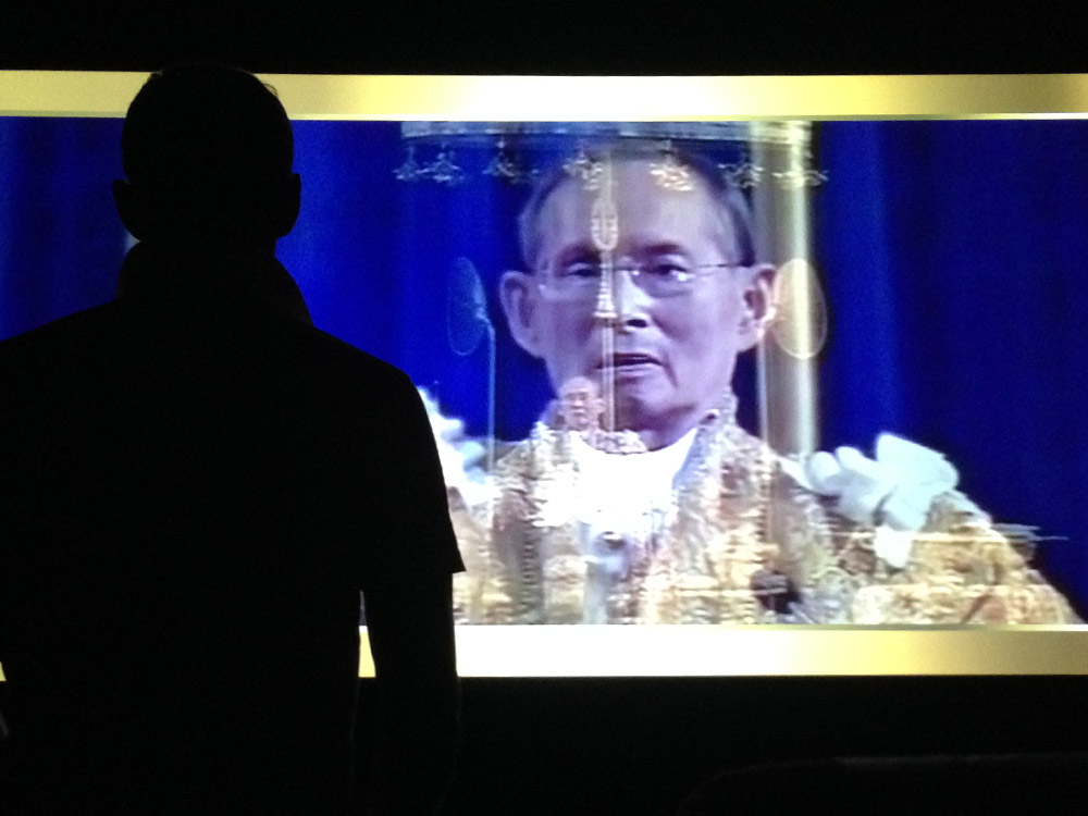 Plötzlich stehen alle auf – auch wir. Es erschallt irre laute thailändische Musik und ein Videoclip, der ästhetisch an 10 Jahre alte Powerpointpräsentationen erinnert. Zu sehen ist der König. König mit Familie. König mit Hund. Noch drei mal König mit Hund. König auf goldenem Stuhl. Nach ca. drei Minuten ist es vorbei. Wir setzten uns wieder hin und machen innerlich einen Hacken hinter dieses kulturelles Event.