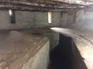Blick in einen kleinen Raum, komplett aus Stein mit einer Art Gang in der Mitte und einer erhöhten Liegefläche