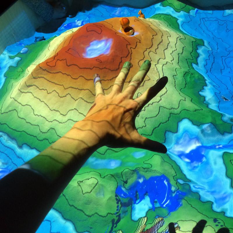 Interaktive Landschaft aus Sand, Projektion und einer Kinekt. Die Hand lässt es regnen.